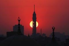 Kairo-Turm und alte Moscheen während des Sonnenuntergangs Stockbilder