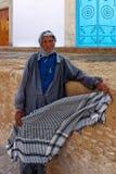 KAIROUAN, TUNESIË - OKTOBER 27, 2010: Een oude Moslimmens het verkopen kefia in Kairouan, Tunesië Stock Afbeelding