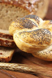Kaiser bread roll with ear of rye on wooden table Royalty Free Stock Photo
