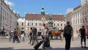 Kaiser Franz mim monumento, turistas e ciclistas no fundo de objetos arquitetónicos da cidade velha filme