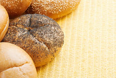 Kaiser Roll. Assorted kaiser rolls form a border. Use yellow place mat for copy. Rolls include plain, poppy seed, and, sesame seed. Selective Focus. Shallow DOF Stock Images