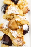 Kaiserschmarrn with plums sprinkled with powdered sugar. Home baked kaiserschmarrn with plums sprinkled with powdered sugar royalty free stock image