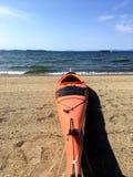 Kajak arancio pronto sulla spiaggia del lago Immagini Stock Libere da Diritti