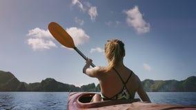 Kajak cercano de los remos de la muchacha de la opinión de la parte trasera a las islas en bahía metrajes