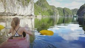 Kajak de los remos de la muchacha de la parte trasera en bahía con verde y Rocky Islands almacen de metraje de vídeo