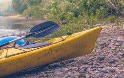 Kajak, der auf Küstenlinie sitzt Stockfotografie