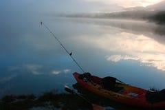 Kajak, der einen nebelhaften See fischt Stockbild