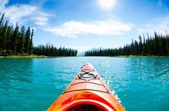 Kajak die op blauw meer varen stock foto