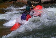 Kajak die in stroomversnelling paddelt Stock Foto's