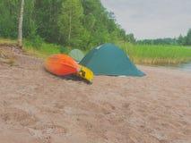 Kajak e tenda sulla sponda del fiume Fotografie Stock Libere da Diritti