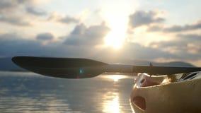 Kajak en la opinión delantera de la playa del kajak del mar en el agua tranquila en la puesta del sol hermosa del verano con los  almacen de video