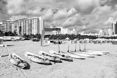 Kajak och surfingbrädor med skovlar på sand royaltyfria foton