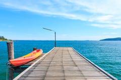 Kajak op Houten Pijler met Blauwe overzees en hemel stock fotografie