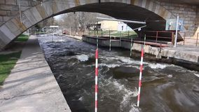 Kajak opleiding, Kajakras dichtbij de brug waar de water sterke draaikolken zich dichtbij de stapels voordoen stock videobeelden