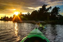 Kajak på en sjö på en brännhet solnedgång Muskoka region Ontario royaltyfria bilder