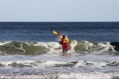 Kajak que practica surf en el mar Imagenes de archivo