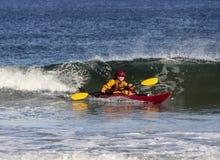 Kajak que practica surf en el mar Fotos de archivo libres de regalías