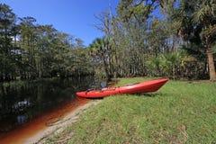 Kajak rosso sull'insenatura di Fisheating, Florida fotografia stock