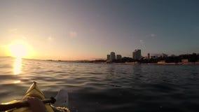 Kajak schwimmt in das Meer bei Sonnenuntergang stock footage