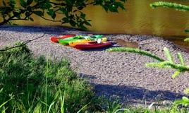 Kajak variopinti che si siedono sul litorale dal lago immagine stock libera da diritti