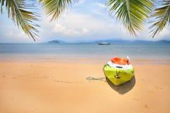 Kajakboot mit Kokosnusspalmblättern auf tropischem Strandhintergrund Lizenzfreie Stockfotografie