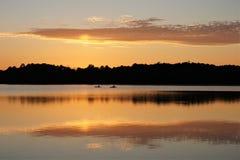 Kajaker på sjön på solnedgången arkivbild