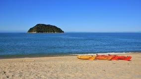 Kajaker på stranden och den lilla ön Arkivfoto