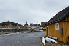 Kajaker som vilar mot senap, färgade huset i den gamla delen av Nuuk, Grönland, Royaltyfri Foto