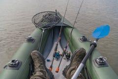 Kajakfischen am See Beine des Fischers auf aufblasbarem Boot mit Angelausr?stung stockfotografie