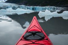 Kajakflyttning till och med isberg i den alpina sjön av Alaska Arkivbilder