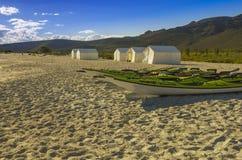 Kajaki odpoczywają na plaży z campingowymi namiotami i pustynnym tłem Obrazy Stock