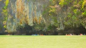 Kajaks con los turistas cerca de la roca enorme con las cuevas almacen de video