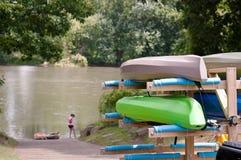 Kajaks die onderaan een helling aan een rivier worden genomen stock afbeelding