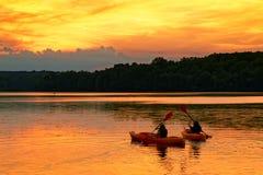 Kajaks en un lago en la puesta del sol Fotos de archivo