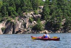 Kajaks femeninos mientras que goza de un lago wilderness. Foto de archivo libre de regalías