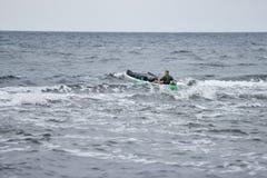 Kajaksurfer over de kam van een golf Royalty-vrije Stock Foto's