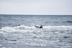Kajaksurfer over de kam van een golf royalty-vrije stock fotografie
