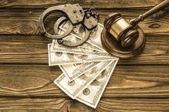 Kajdanki, dolarowi rachunki, sędziego ` s młot przeciw tłu zdjęcie royalty free