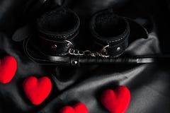 Kajdanki i bat dla BDSM płci z czerwonymi sercami fotografia stock