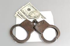 Kajdanki i biała koperta z pieniądze na szarość Fotografia Royalty Free