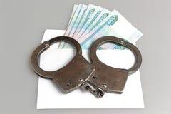 Kajdanki i biała koperta z pieniądze na szarość Zdjęcia Royalty Free