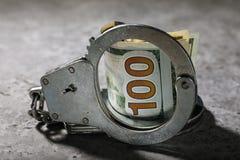 Kajdanki i sto dolarowi rachunków na stole Pojęcie na temacie oszukańcze transakcje z pieniądze fotografia royalty free
