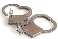 Kajdanki w kierowym kształcie i kluczu wśród odosobnionego Zdjęcie Stock