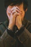 Kajdanowy męski więzień w wojskowym uniformu ono modli się Zdjęcie Stock