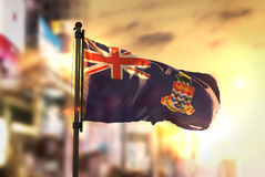 Kajman wysp flaga Przeciw miasta Zamazanemu tłu Przy wschodu słońca b Obrazy Stock