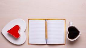 Kaka för kaffekopp i hjärtaform och anteckningsbok Arkivbild