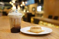 Kaka f?r mutterkaramellm?ne med islattekaffe bredvid, p? tr?tabellen royaltyfri foto