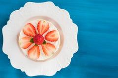 Kaka för sommarjordgubbemousse med nya bär på den bästa sikten för träblå bakgrund Royaltyfri Foto
