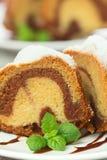 Kaka för vaniljang-choklad som skivas med mintkaramelllaves på träflik Royaltyfri Bild