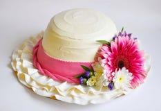 Kaka i form av en kvinnlig vit hatt med ett rosa band och en blommaprydnad Royaltyfri Bild